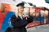 The rail transport conductor is checking time on railroad station.