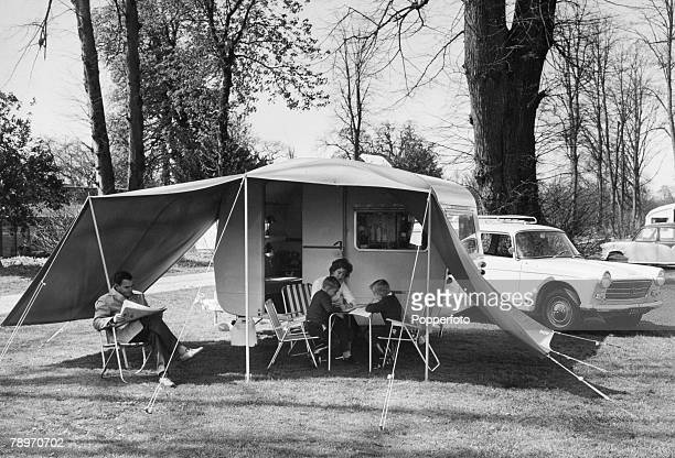 Transport England Circa 1950's A family on camping holiday sit outside their caravan with its awning attached