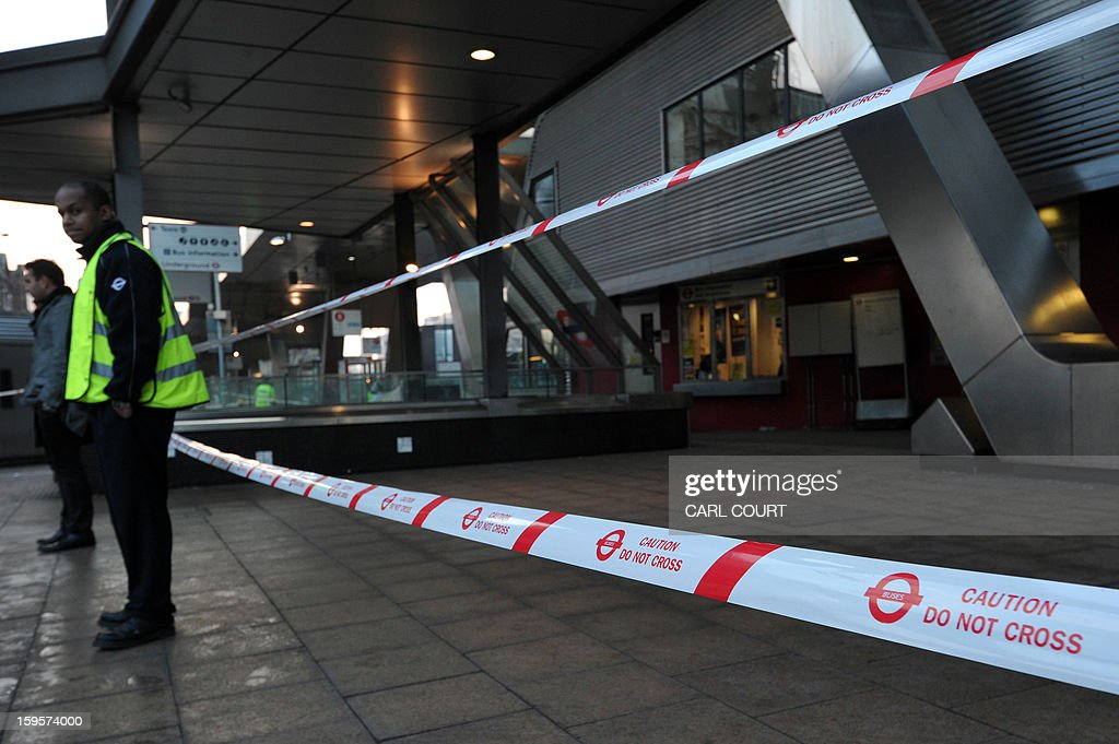 A Transport For London (TFL) employee stands next to a cordon at Vauxhall underground station near the scene of a helicopter crash in central London on January 16, 2013. Two people were killed when a helicopter hit a crane at a building site in central London during morning rush hour and plunged to the ground in a ball of flames. AFP PHOTO / CARL COURT
