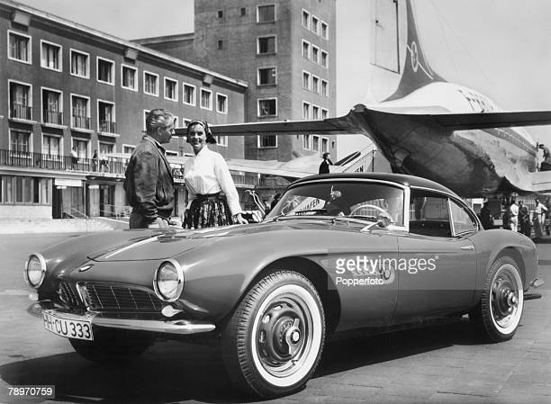 Transport Germany Circa 1950's The BMW 507 roadster sports car seen here parked behind an airliner at an airport