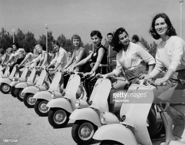 circa 1955 A line up of Vespa motor scooters with young ladies
