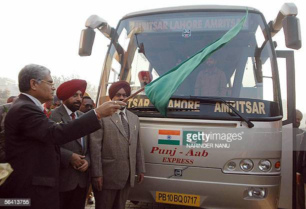 Transport Secretary of India's northern state of Punjab A R Talwar waves a green flag in front of a bus carrying local officials on its way to cross...
