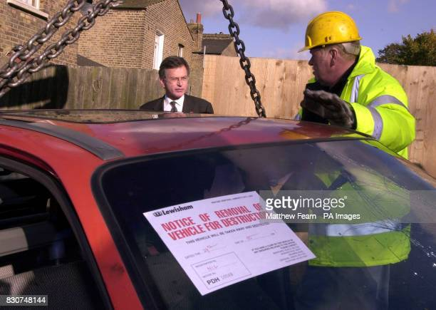 Transport Secretary Stephen Byers watches an one of Britain's abandoned cars is lifted onto a lorry in Catford London Byers launched a package of...