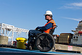Transportation engineer in a wheelchair inspecting shipping containers at shipping port