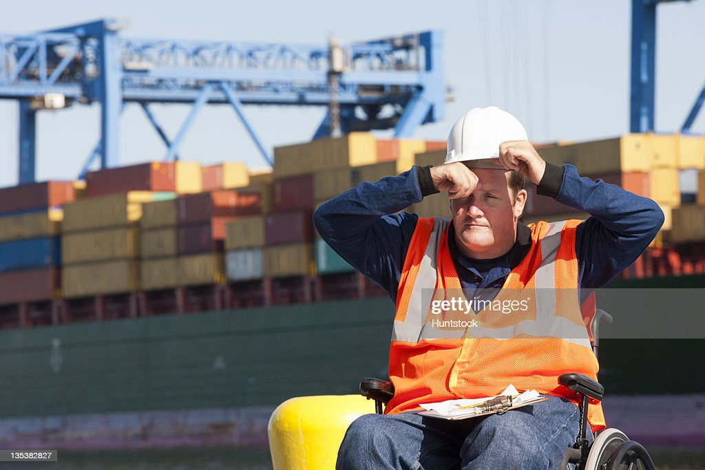 Transportation engineer in a wheelchair recording data for shipping containers and experiencing hot sun : Stock Photo