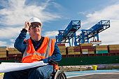 Transportation engineer in a wheelchair studying plans at shipping port