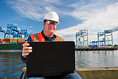 Transportation engineer in wheelchair recording data on laptop at shipping port