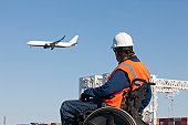 Transportation engineer in wheelchair watching airliner flying over shipping containers and cranes at port