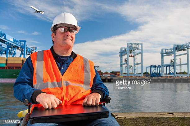 Transportation engineer in wheelchair with a laptop at shipping port