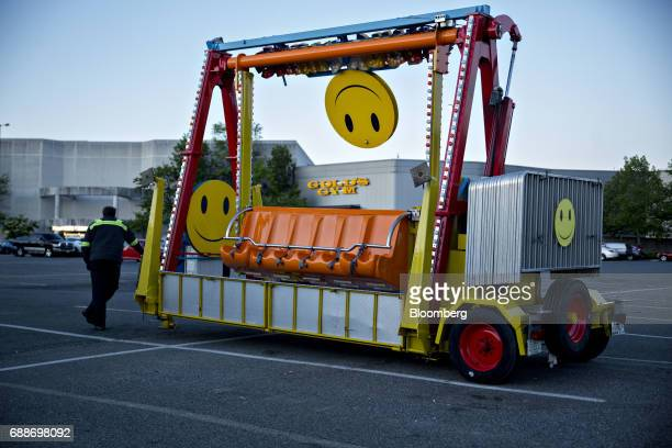 A transportation manager stands next to the Happy Swing ride before it is hitched to a semitrailer truck after the Dreamland Amusements carnival in...