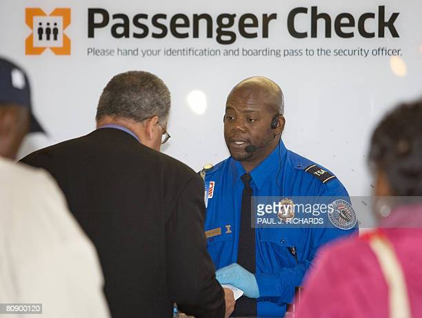 Transportation Safety Administration Officer Donald Boone wearing a new dark blue uniform shirt and new badge checks the identity papers of a airline...
