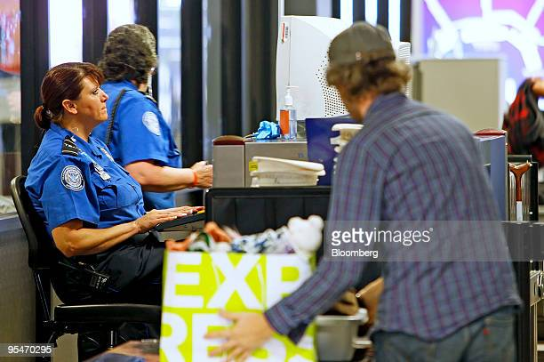 A Transportation Safety Administration officer left operates an xray machine at a security check point at the Salt Lake International Airport in Salt...