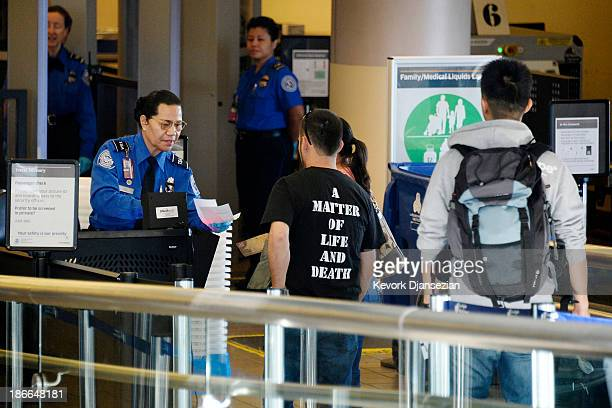 Transportation Security Administration agent checks the boarding pass of a traveler after Terminal 3 was reopened a day after a shooting at Los...