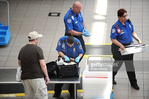 A Transportation Security Administration agent checks the luggage of a passenger May 2 2011 at Orlando International Airport in Orlando Florida...