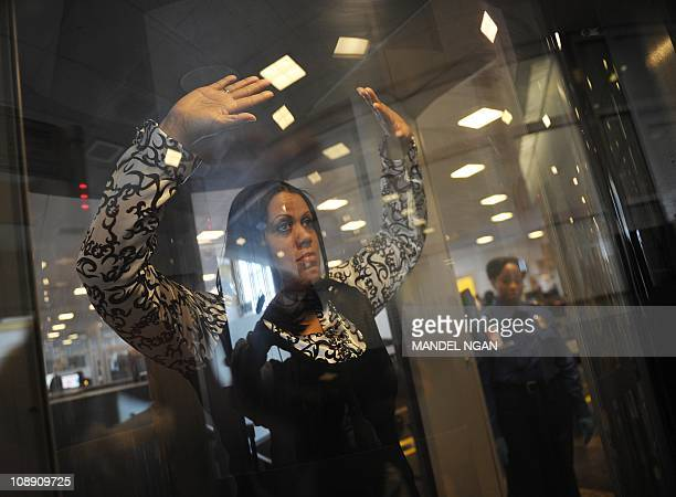 A Transportation Security Administration agent keeps watch as a woman raises her arms while being scanned in an advanced imaging technology machine...