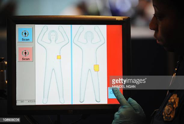 A Transportation Security Administration agent looks at the monitor of an advanced imaging technology machine during a demonstration of the machines'...