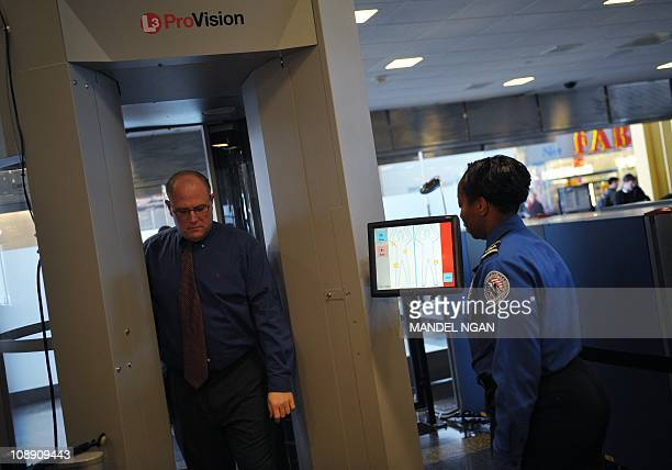 A Transportation Security Administration agent looks at the monitor of the advanced imaging technology machine as a man steps through the machine...