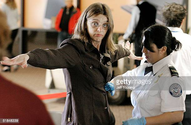 Transportation Security Administration agent performs a patdown check on an airline passenger at a security checkpoint in terminal four at Phoenix...