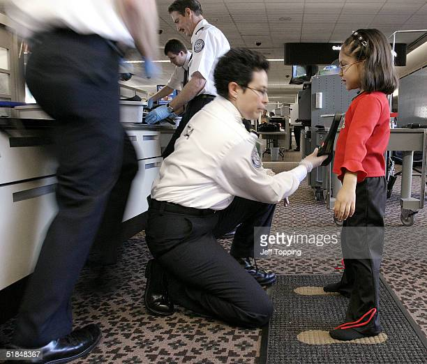 Transportation Security Administration agent performs a patdown check on a young girl at a security checkpoint in terminal four at Phoenix Sky Harbor...