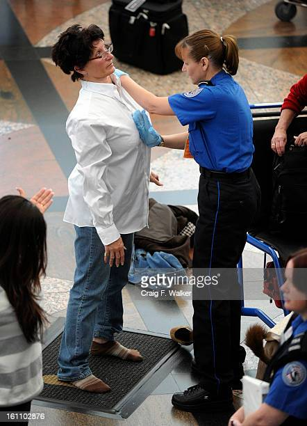 Transportation Security Administration agent performs an enhanced pat down on a commuter at a security area at Denver International Airport in Denver...