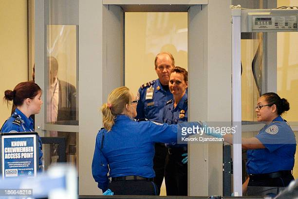 Transportation Security Administration agents celebrate after Terminal 3 was reopened a day after a shooting at Los Angeles International Airport...