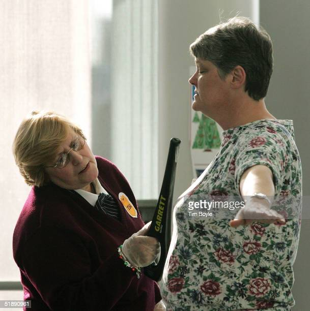 S Transportation Security Administration employee passes a metaldetecting wand over a female traveler's chest at O'Hare International Airport...