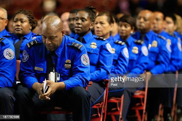 Transportation Security Administration officer bows his head as he sits alongside colleagues during the public memorial for Transportation Security...