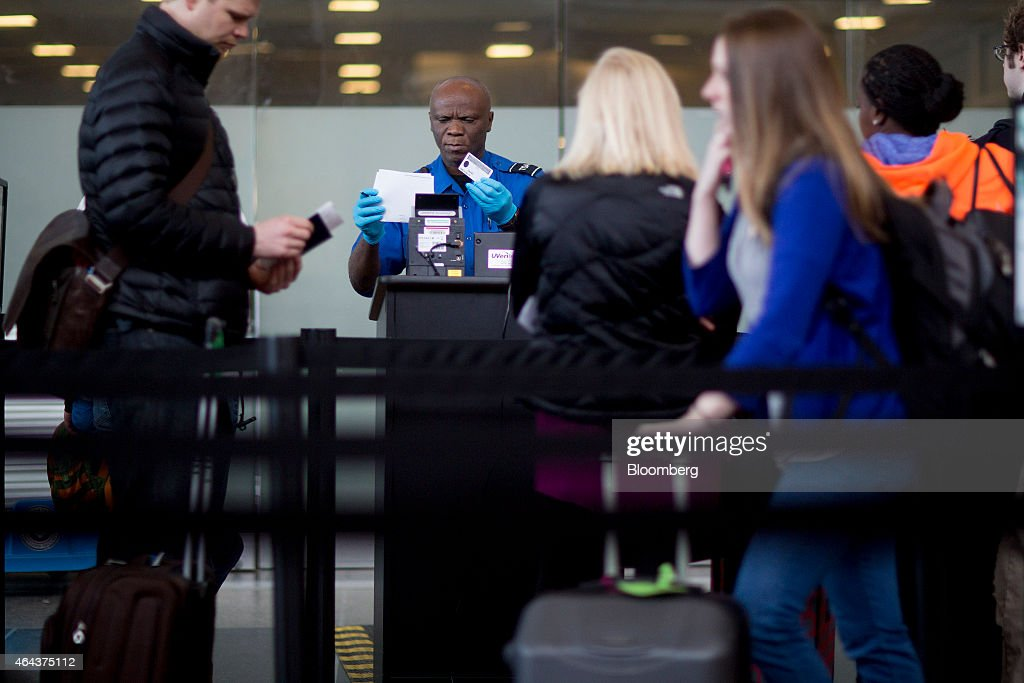 a transportation security administration tsa officer checks a passengers identification and boarding pass at - Transportation Security Officer