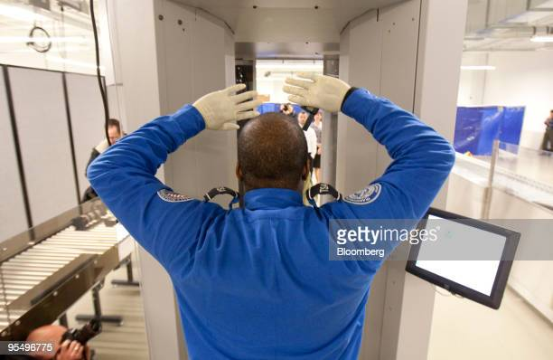 A Transportation Security Administration officer demonstrates how to walk through the ProVision Millimeter Wave advanced imaging technology machine...