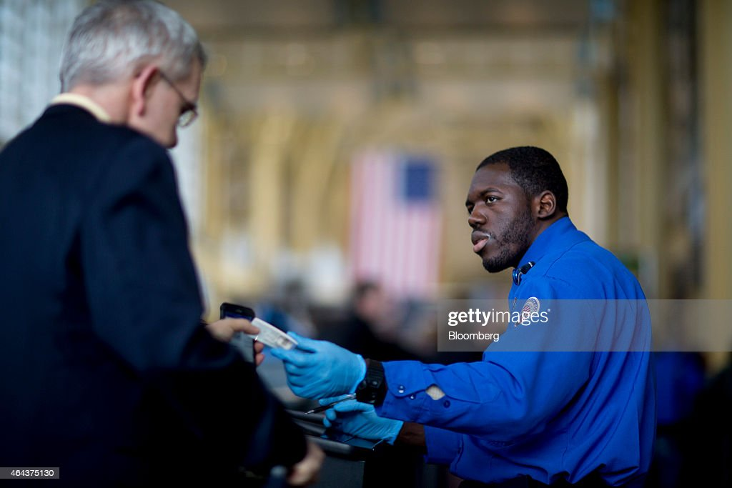 a transportation security administration tsa officer hands a passenger his identification at a security - Transportation Security Officer