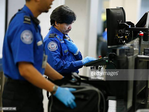 a transportation security administration officer monitors a computer screen as passengers bags are scanned at - Transportation Security Officer