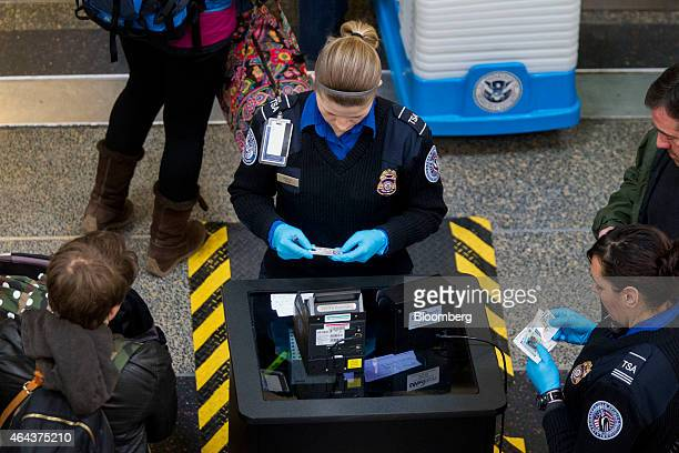 Transportation Security Administration officers check passenger's identification at a security checkpoint at Ronald Reagan National Airport in...
