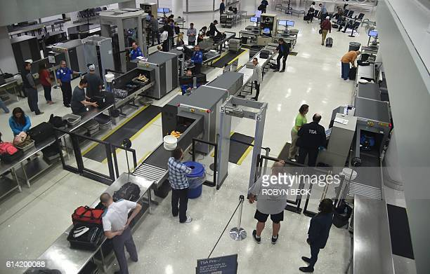 US Transportation Security Administration officers inspect airline passengers before they board their flights at LambertSt Louis International...