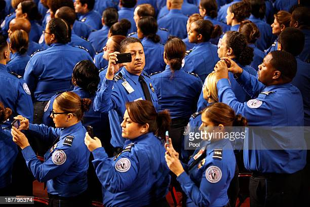 Transportation Security Administration officers take photos as a TSA honor guard enters the Los Angeles Sports Arena signaling the start of the...