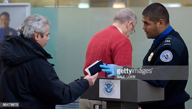 A Transportation Security Administration official checks the identification of passengers prior to entering a security checkpoint at Ronald Reagan...