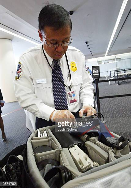 Transportation Security Administration screener inspects a camera bag at the international terminal of San Francisco International Airport August 5...