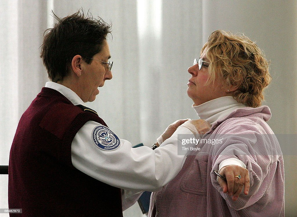 A Transportation Security Administration (TSA) worker Denise Thieben (L) checks a traveler at her security post at O'Hare International Airport December 22, 2005 in Chicago, Illinois. The TSA announced today that their passenger screening process has been amended to once again allow items such as scissors and small tools to be carried onto planes.