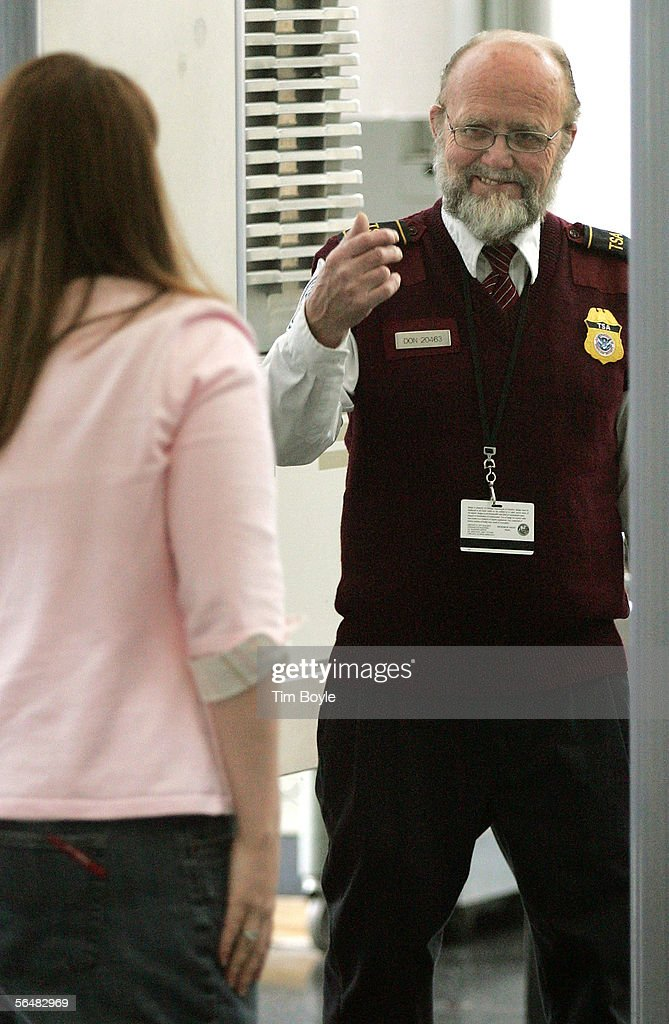 Transportation Security Administration (TSA) worker Donald Reid beckons a traveler to pass through a metal detector at his security post at O'Hare International Airport December 22, 2005 in Chicago, Illinois. The TSA announced today that their passenger screening process has been amended to once again allow items such as scissors and small tools to be carried onto planes.
