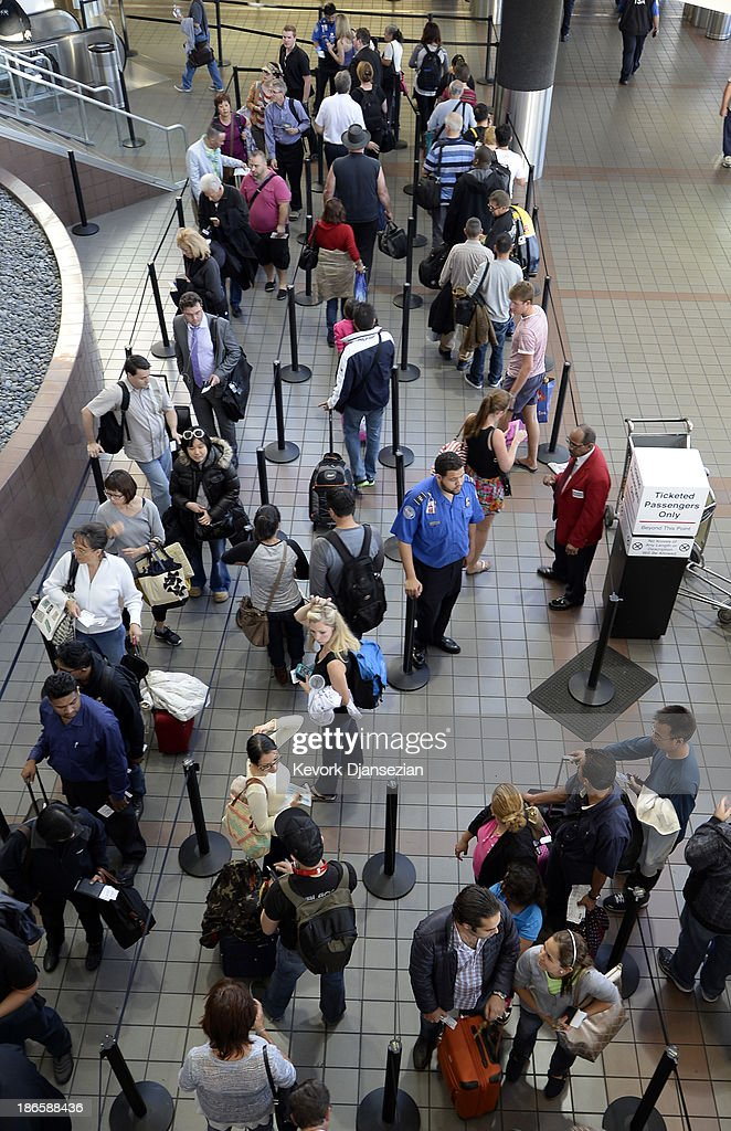 A Transportation Security Administration worker stands in the middle of a group of stranded passengers waiting to get screened as normal operations slowly return after a shooting incident at Los Angeles International Airport (LAX) November 1, 2013 in Los Angeles, California. A man identified as Paul Ciancia reportedly pulled out an assault rifle in Terminal 3 of the airport and shot his way through security, killing one Transportation Security Administration (TSA) worker and wounding several others before being shot himself.
