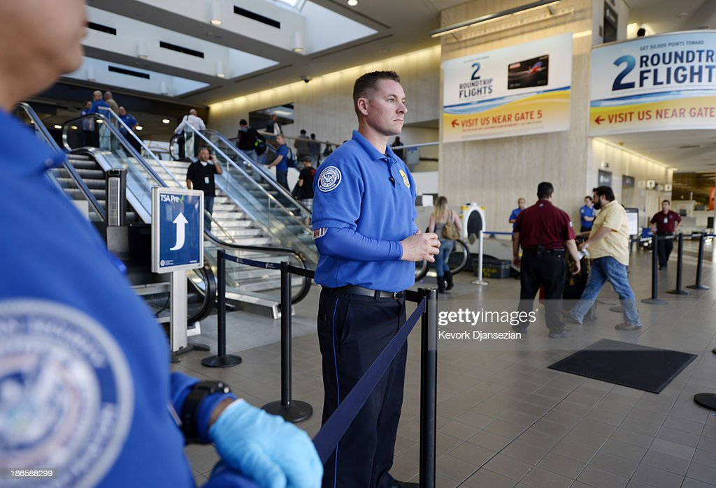 Transportation Security Administration workers keep a look out as stranded passengers begin to arrive at the departure terminal as normal operations slowly return after a shooting incident at Los Angeles International Airport (LAX) November 1, 2013 in Los Angeles, California. A man identified as Paul Ciancia reportedly pulled out an assault rifle in Terminal 3 of the airport and shot his way through security, killing one Transportation Security Administration (TSA) worker and wounding several others before being shot himself.