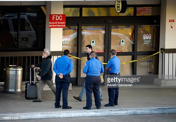 Transportation Security Administration workers stand in front of the blocked off Terminal 3 entrance as law enforcement officials continue to...