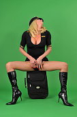 Transsexual airline pilot wearing sexy boots on a green screen