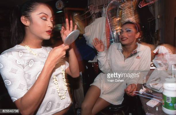 Transsexual and transvestite performers joke as they put the finishing touches on their makeup before going onstage for a cabaret show at a nightclub...