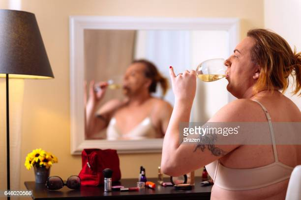 Transsexual person putting make up on in front of the mirror at home
