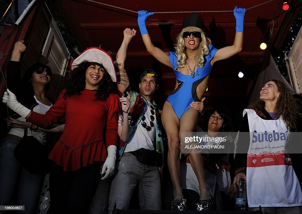A transvestite (C) characterized as the pop music star Lady Gaga dances during the XXI Gay Pride Parade, at Mayo square in Buenos Aires on November 10, 2012. AFP PHOTO / Alejandro PAGNI