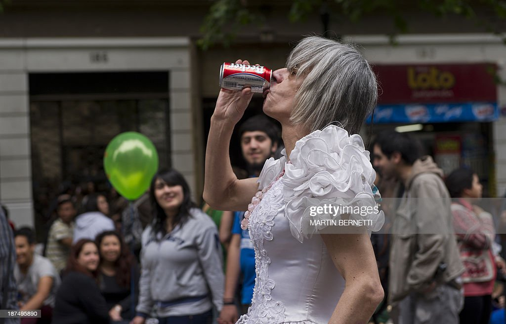 A transvestite drinks a beer in Plaza Bulnes, in Santiago, during the VIII Gay Pride Parade, on November 9, 2013.