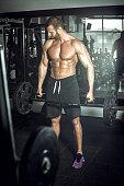 Professional bodybuilder doing trap bar deadlift exercise in modern fitness center. Toned image.