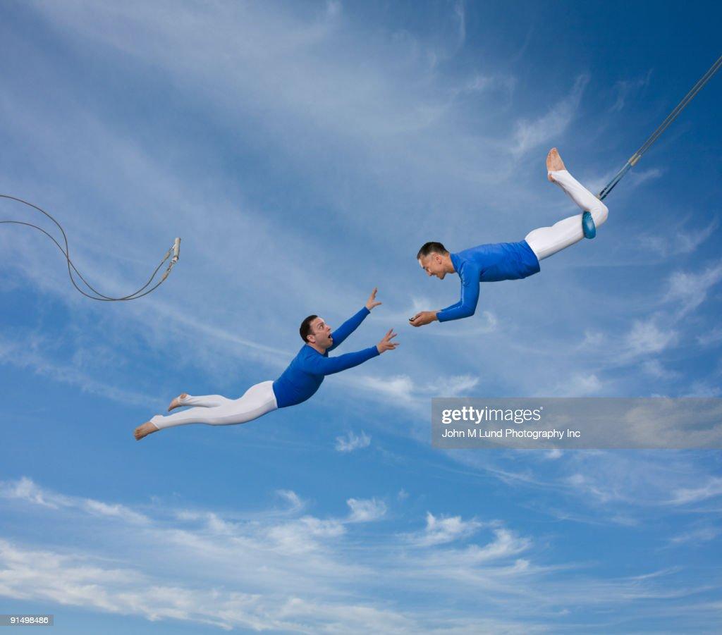 Trapeze artist watching partner fall
