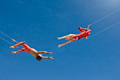 Trapeze artists swinging towards one another, low angle view