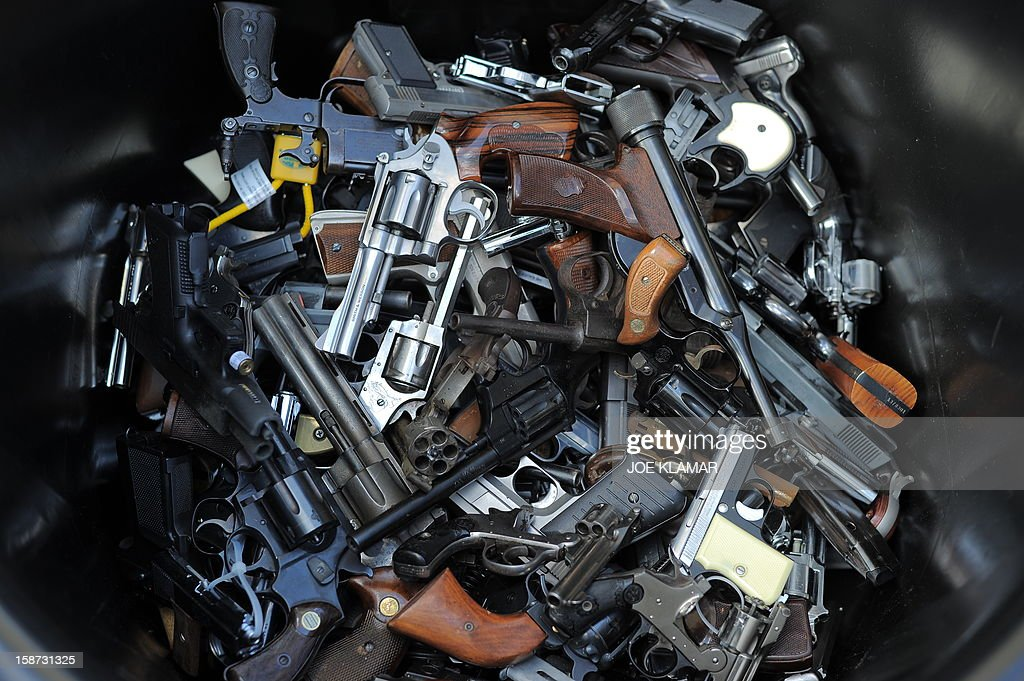 A trash bin full of handguns collected during the LAPD Gun Buyback Program event in Van Nuys area, north of Los Angeles, on December 26, 2012. By noon LAPD collected more then 420 handguns, rifles and shotguns such as TEC-9, Assault rifle, Uzi, WWI rifle. Apart from it, there are 16 assault weapons and some vintage weapons. One is dated 1895. AFP PHOTO / JOE KLAMAR